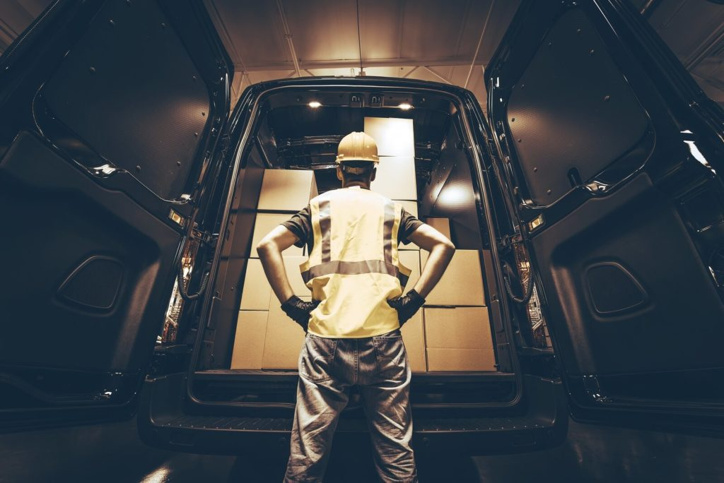worker with safety gears inspecting the cargo van